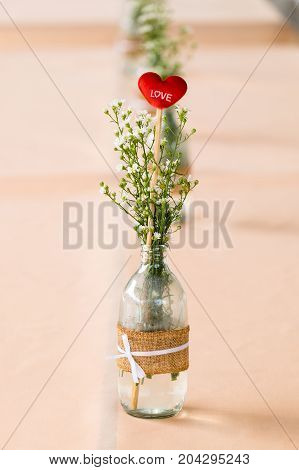 Love and heart sign in a flower bottle on the dinner table wedding decoration.