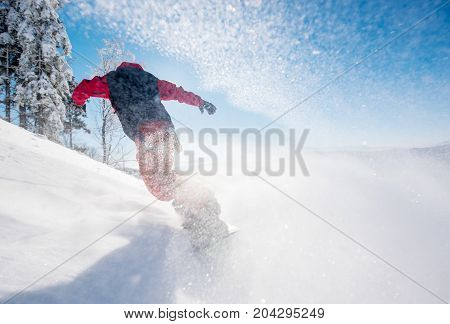 Horizontal Low Angle Shot Of A Snowboarder Riding The Slope On A Sunny Winter Day In The Mountains.