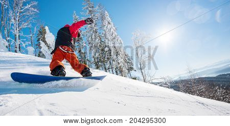 Horizontal Low Angle Shot Of A Male Snowboarder Riding The Slope On A Sunny Winter Day In The Mounta