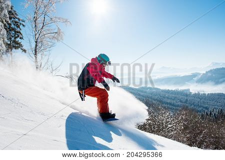 Shot Of A Male Snowboarder Enjoying Riding In Mountains In The Morning On A Sunny Winter Day Copyspa