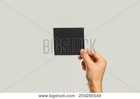 Male Hands Holding A Black Sheet Of Paper. Isolated On Gray Background. Closeup