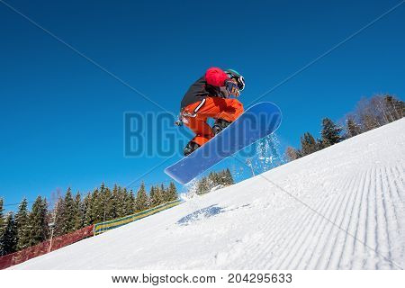 Low Angle Shot Of Man Snowboarder Jumping In The Air While Snowboarding On The Slope At Ski Resort I