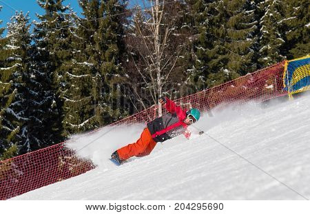 Professional Snowboarder Riding The Slope In The Mountains. Forest On The Background. Freeride Snowb
