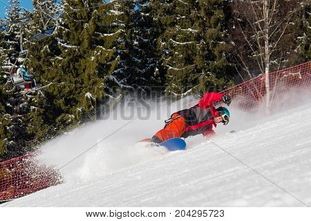 Freerider Snowboarder Skiing The Slope At Winter Resort In The Mountains. Forest On The Background.