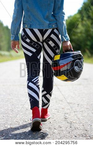 A girl carries a motorcycle helmet in his hand. You only see the legs. Closeup.