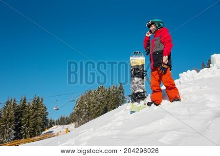 Male Snowboarder Resting On The Slope Of The Hill, Talking On The Phone On A Beautiful Sunny Winter