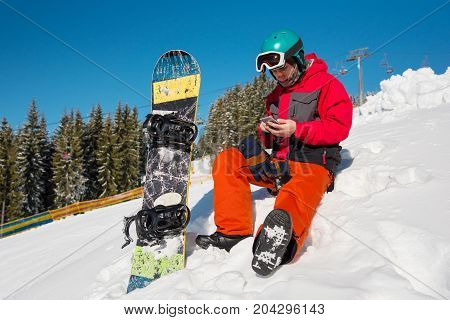 Snowboarder Sitting In The Snow At Ski Resort,using His Smart Phone While Resting In The Mountains T