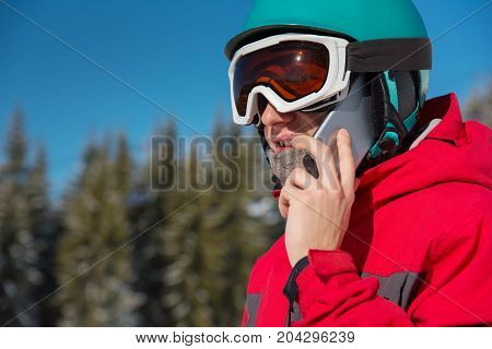 Close-up Shot Of A Snowboarder Talking On The Phone, Wearing Helmet, Skiing Mask And Colorful Winter