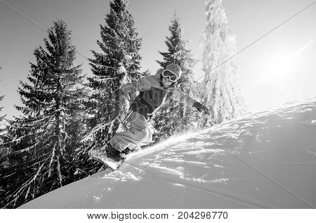 Monochrome shot of a man snowboarder skiing the in the mountains copyspace extreme winter sports adrenaline activity lifestyle sportspeople freeride concept poster