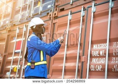 Foreman control loading Containers box from Cargo freight ship for logistics import export background.