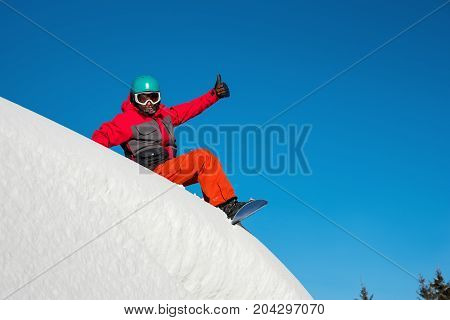 Shot Of A Happy Snowboarder Sitting In The Snow On Top Of The Mountain Showing Thumbs Up