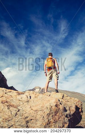 Man celebrating beautiful inspiring view in mountains. Hiker or climber looking at inspirational landscape on rocky trail on Tenerife Canary Islands.
