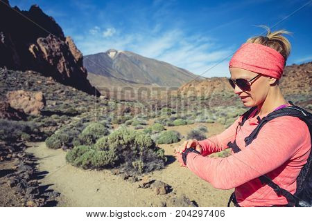 Trail running woman on mountain trail looking at sportwatch checking performance heart pulse or GPS position nd track. Cross country running in beautiful nature Canary Islands.