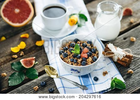 Muesli with blueberries on a napkin with a cup of coffee, a pitcher of milk and fruit in the background