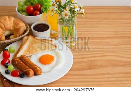 Homemade breakfast with sunny side up fried egg toast sausage fruits vegetable strawberry jam and orange juice. Delicious american breakfast concept for background or wallpaper. American breakfast on breakfast table with copy space.
