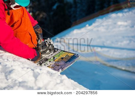Close-up Shot Of A Snowboarder Preparing Snowboard For Riding Downhill At Winter In The Mountains