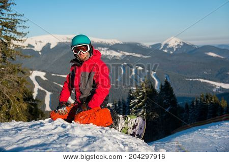Shot Of A Male Snowboarder Resting After Riding On The Slope In The Mountain Ski Resort Bukovel On A