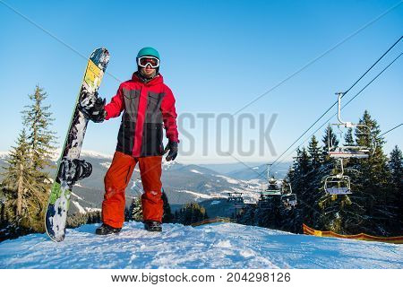 Full Length Portrait Of Male Snowboarder, Looking To The Camera, Resting After Riding It The Mountai