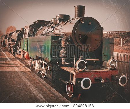 The old locomotive stands on the railway. Stylized toned photo.
