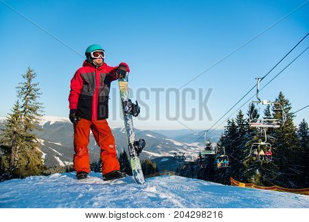 Full Length Portrait Of A Snowboarder Wearing Helmet Skiing Mask And Colorful Winter Snowboarding Cl