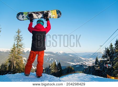 Rearview Full Length Shot Of A Snowboarder Standing In The Mountains Holding Up His Snowboard In The
