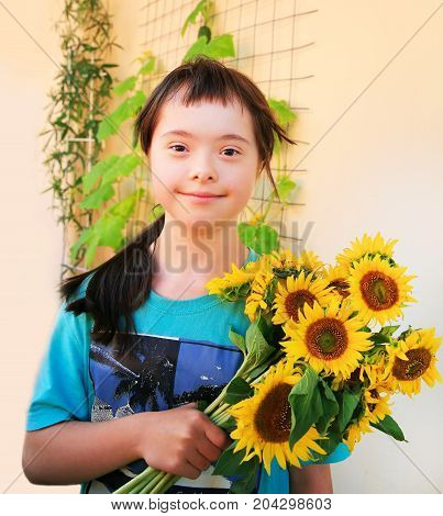 Down syndrome girl with sun flowers .