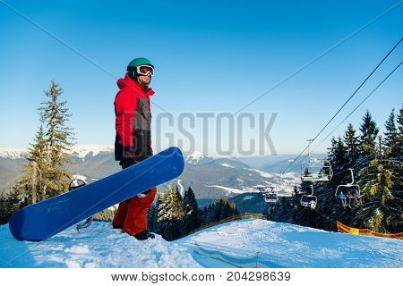 Man Snowboarder Standing With His Snowboard On Snowy Slope In The Mountains Looking Around Enjoying