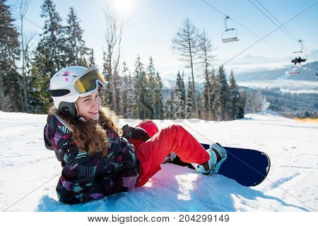 Smiling Female Snowboarder Lying On The Snow Under A Ski Lift In The Sun Rays On A Beautiful Sunny W