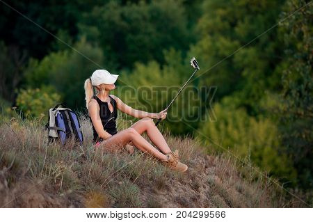 Young girl backpacker sitting on top of the hill with backpack next to her take selfie with the selfie stick and enjoys the nature. Forest background
