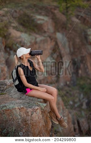 Young woman tourist with backpack sitting on edge of a cliff and drinking water. Mountain background