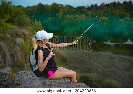 Young girl backpacker sitting on top of the hill takes selfie with the selfie stick and enjoys the nature. Misty forest background