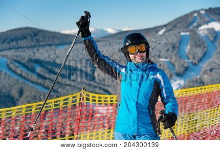 Smiling Girl Enjoying Ski Holiday Standing On The Snowy Mountain And Raised Her Hand Up At Sunny Day
