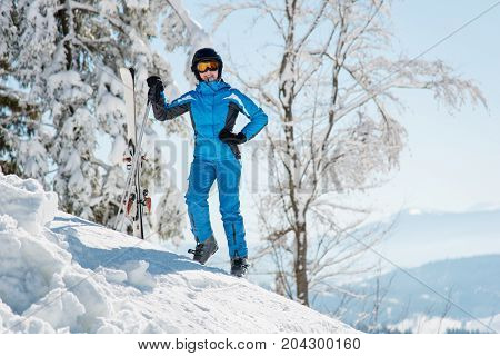 Full Length Shot Of A Smiling Female Skier Resting The Slope With Her Skis In The Mountains At Winte