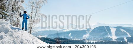 Panoramic Shot Of A Female Skier Resting On Top Of The Mountain Observing Nature At Ski Resort On A