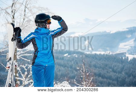 Close-up Portrait Of Female Skier With Skis Enjoying Stunning Scenery In The Mountains Looking Away,