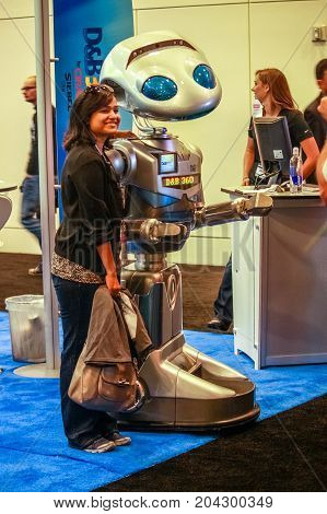 SAN FRANCISCO CA US - OCT 3 2012: Unidentified woman stands near robot at booth of Dun and Bradstreet company at exhibition of Oracle OpenWorld conference in San Francisco on October 3 2012.