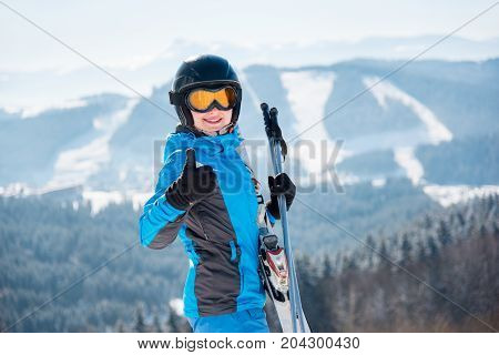 Close-up Portrait Of Female Skier In A Ski Mask Smiling Showing Thumbs Up At Winter Ski Resort In Th