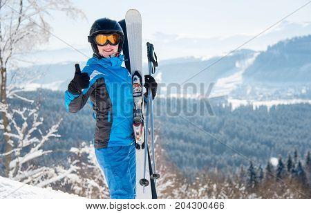Happy Female Skier Wearing Blue Ski Suit, Black Helmet And Mask Smiling Showing Thumbs Up Posing In