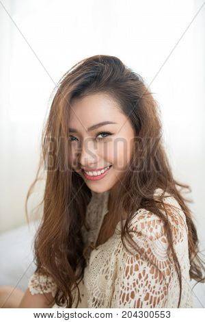 Asian Woman Breathing And Sitting On A Bed At Home With A Window In The Background