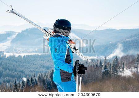 Rear View Female Skier Holding Skis On The Shoulder, Wearing Blue Ski Suit And Black Helmet, Resting