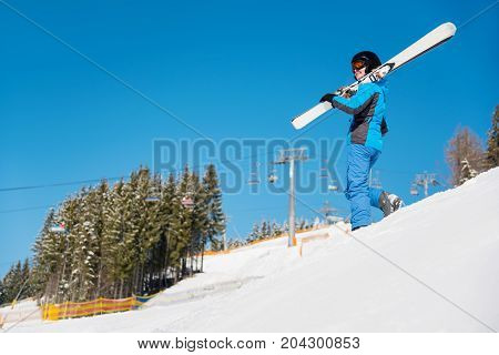 Low Angle Shot Of A Woman Walking Down The Hill In Snowy Mountains Carrying Her Skis On The Shoulder