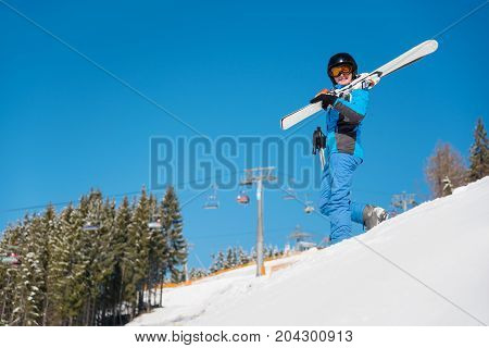 Happy Young Sportswoman Skier Standing The Snowy Slope At Ski Resort In The Mountains, Holding Her S