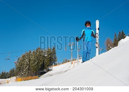 Full Length Portrait Of A Happy Female Skier Standing With Her Skis On The Slope, Smiling To The Cam