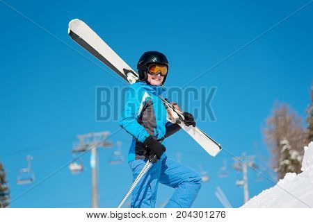 Close-up Shot Of A Cheerful Female Skier Carrying Her Skis Smiling To The Camera, Enjoying Skiing At