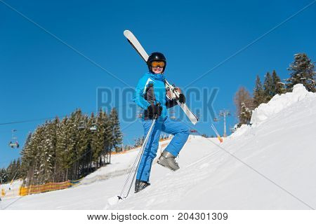 Low Angle Full Length Shot Of A Cheerful Woman Skier Carrying Her Skis Smiling To The Camera While W