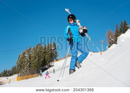 Full Length Shot Of A Cheerful Female Skier Carrying Her Skis On The Shoulder, Enjoying Skiing At Sk