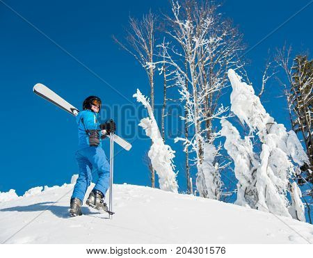 Shot Of A Female Skier Enjoying Stunning View Of Snowy Mountains While Walking Up The Slope Carrying