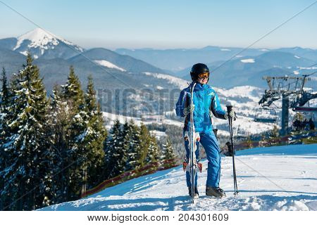 Full Length Shot Of A Female Skier In Winter Sportswear Posing On Top Of A Mountain With Her Skis Co