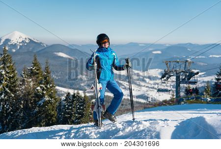 Full Length Shot Of A Happy Female Standing With Her Skis On Top Of The Mountain At Ski Resort, Smil