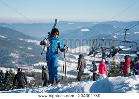 Full Length Shot Of A Happy Woman Posing With Her Skis On The Shoulder On Top Of The Hill, Smiling J